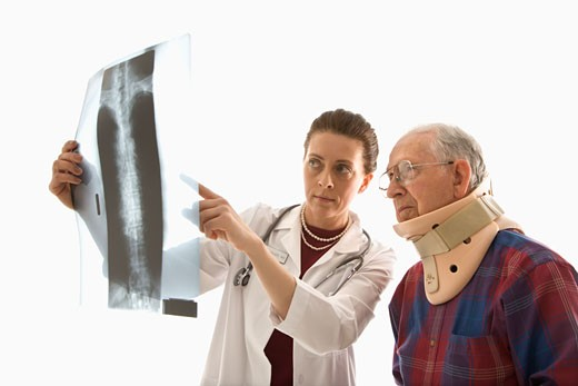 Mid-adult Caucasian female doctor ponting at x-ray with elderly Caucasian male in neck brace looks on. : Stock Photo