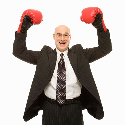 Stock Photo: 1525R-103297 Smiling Caucasian middle-aged businessman standing with arms raised wearing boxing gloves.
