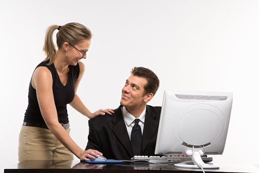 Stock Photo: 1525R-103407 Caucasian mid-adult woman touching mid-adult man's shoulder and using mouse at computer.