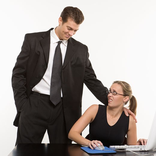 Caucasian mid-adult man sexually harassing woman sitting at computer. : Stock Photo