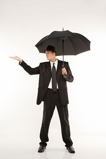 Stock Photo: 1525R-103440 Caucasian mid-adult businessman wearing fedora holding umbrella with arm outstretched.