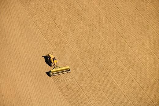 Stock Photo: 1525R-104073 Aerial of farmer tilling crop field in farmland, USA.