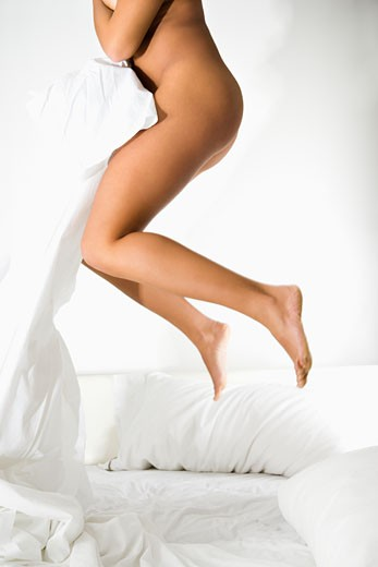 Stock Photo: 1525R-104247 Nude woman holding white sheet jumping on bed.