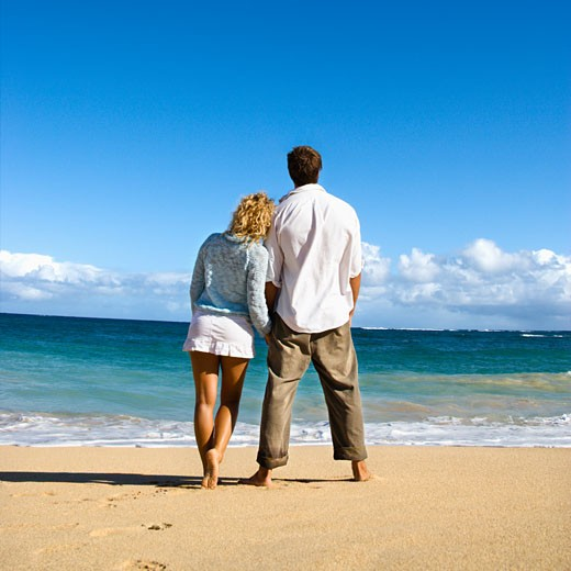 Stock Photo: 1525R-104255 Attractive couple standing leaning on eachother looking out at ocean in Maui, Hawaii.