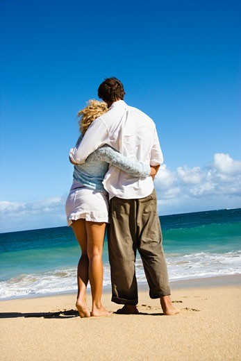 Attractive couple standing embracing looking out at ocean in Maui, Hawaii. : Stock Photo