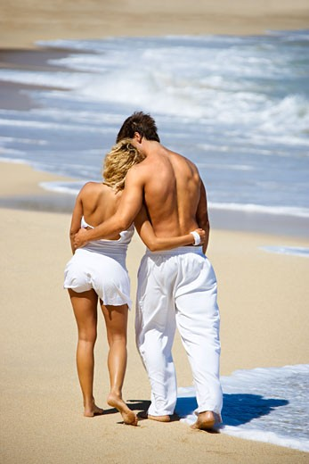 Stock Photo: 1525R-104308 Attractive couple walking on Maui, Hawaii beach with arms around eachother.
