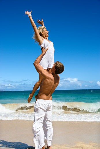 Stock Photo: 1525R-104310 Man holding woman up in air on Maui, Hawaii beach.