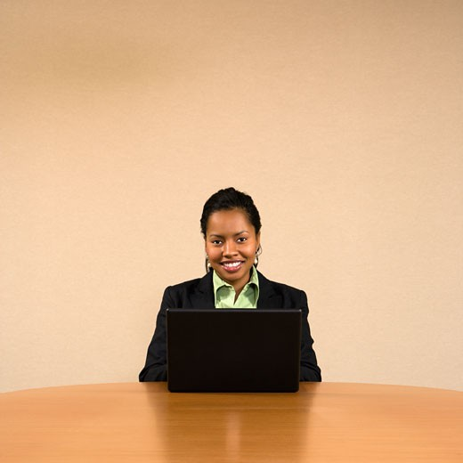 Stock Photo: 1525R-104510 Businesswoman sitting at conference table smiling and typing on laptop computer.