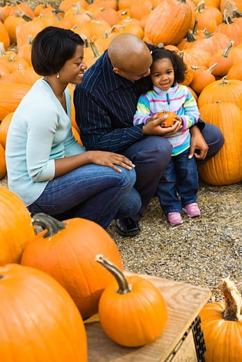 Parents and daughter picking out pumpkin and smiling at outdoor market. : Stock Photo