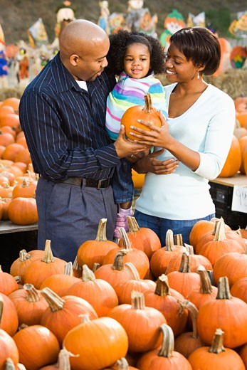 Stock Photo: 1525R-104583 Parents and daughter picking out pumpkin and smiling at outdoor market.