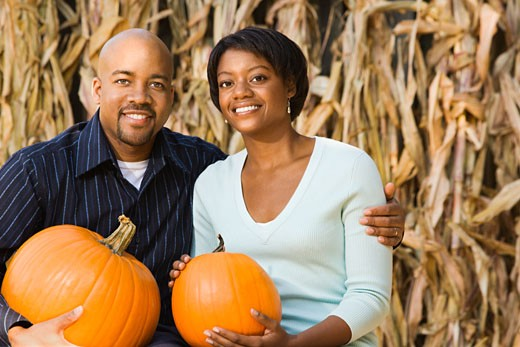 Stock Photo: 1525R-104590 Happy smiling couple sitting on hay bales and holding pumpkins at outdoor market.