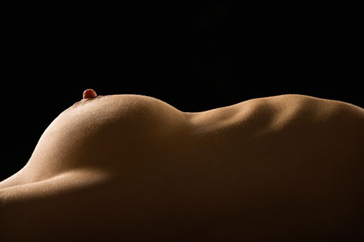Stock Photo: 1525R-105046 Side view of torso of nude Caucasian woman lying on back.