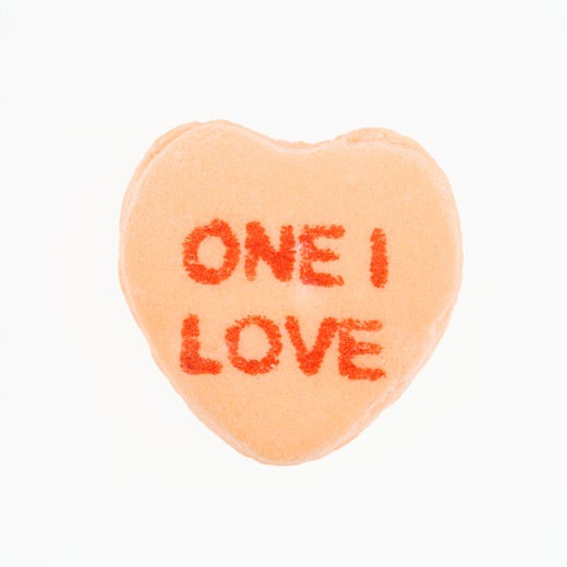 Orange candy heart that reads one I love against white background. : Stock Photo