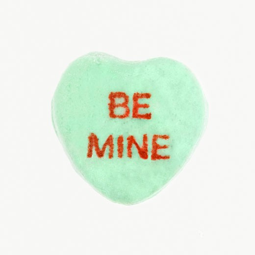 Green candy heart that reads be mine against white background. : Stock Photo