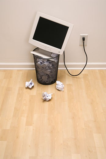 Stock Photo: 1525R-105283 Computer monitor in trash can surrounded by crumpled up paper.
