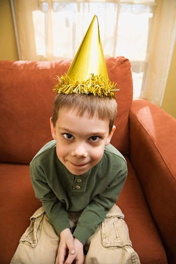 Stock Photo: 1525R-105351 Caucasian boy with party hat looking at viewer and making facial expression.