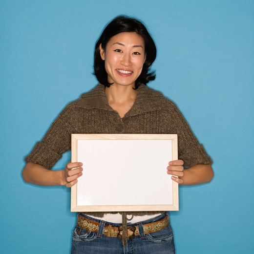 Pretty Asian mid adult woman holding blank sign on blue background. : Stock Photo