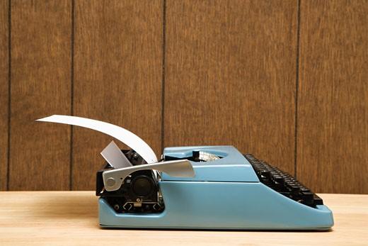 Vintage blue typewriter on desk with wood paneling. : Stock Photo