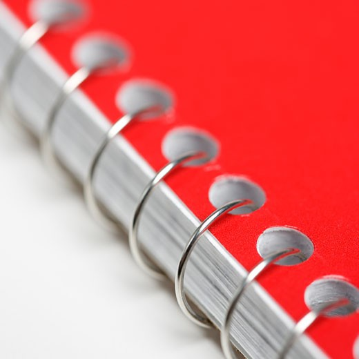 Stock Photo: 1525R-106192 Close up red spiral bound notebook.