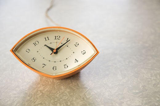 Stock Photo: 1525R-106257 Still life of orange eye-shaped vintage clock on table.