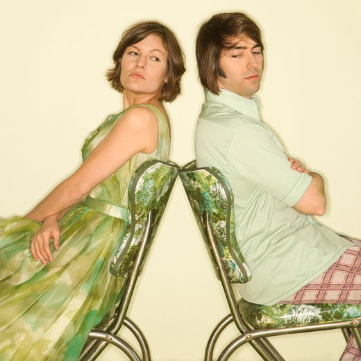 Caucasian mid-adult couple wearing vintage clothing sitting back to back in green vinyl chairs with arms crossed looking angry. : Stock Photo