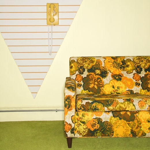 Stock Photo: 1525R-106418 Retro floral printed sofa with yellow rotary phone hanging on wall.