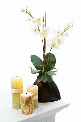 Still life of yellow candles and white lillies. : Stock Photo