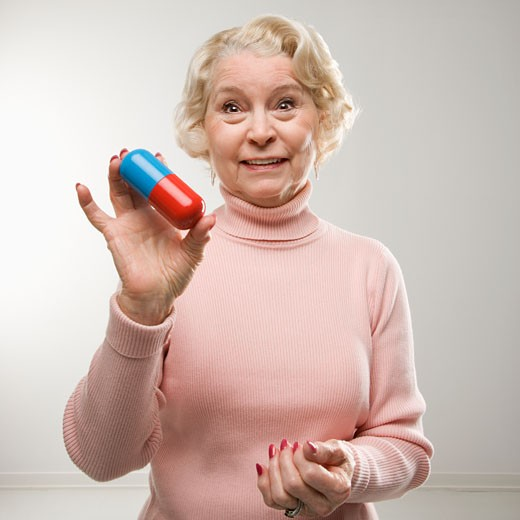 Caucasian senior woman holding oversized pill at viewer. : Stock Photo