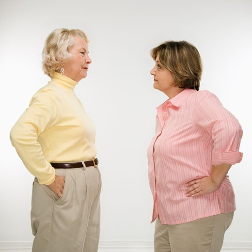 Caucasian senior woman and middle aged woman face to face arguing. : Stock Photo