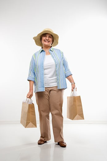 Caucasian middle aged woman holding gift bags smiling at viewer. : Stock Photo