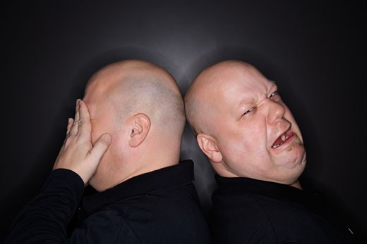 Caucasian bald mid adult identical twin  men standing back to back with sad expressions. : Stock Photo