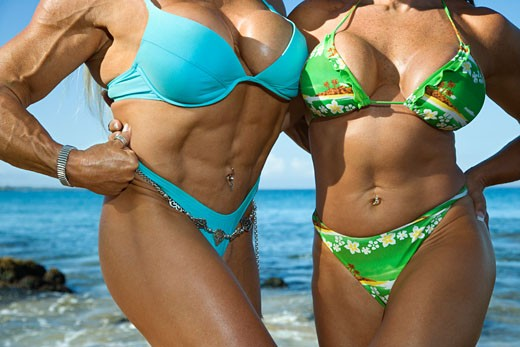 Stock Photo: 1525R-107130 Close up torsos of Caucasian mid adult women bodybuilders in bikinis standing on Maui beach.