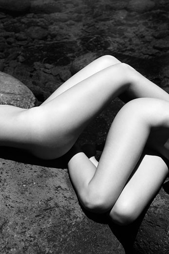 Close up of two young adult nude Caucasian women lying on boulders in Maui. : Stock Photo