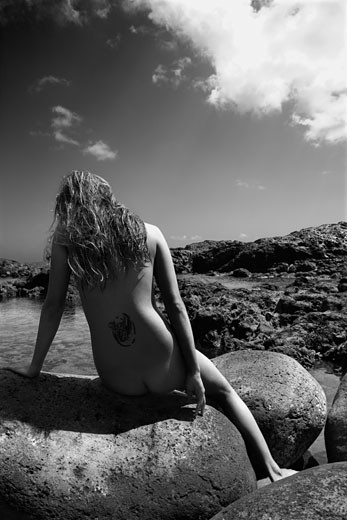 Stock Photo: 1525R-107405 Back view of young nude Asian woman sitting on rocks in Maui, Hawaii.