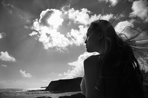 Young nude Asian woman looking out towards ocean with hair blowing in wind. : Stock Photo