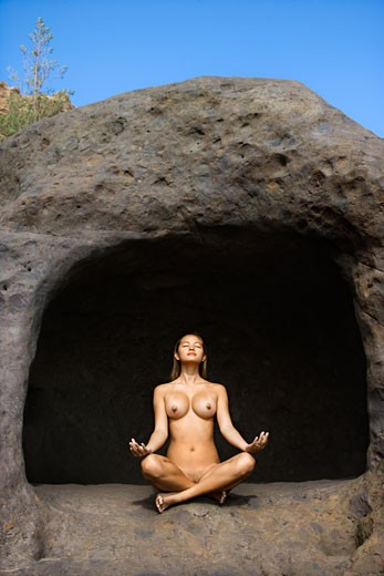 Stock Photo: 1525R-107431 Young nude Asian woman mediatating with legs crossed in cave.
