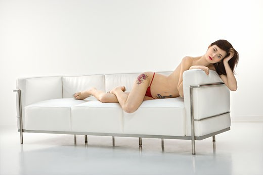 Portrait of attractive  redhead Caucasian young woman lying on sofa in thong. : Stock Photo