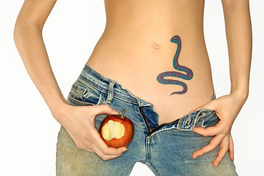 Stock Photo: 1525R-107545 Portrait of attractive Caucasian young woman holding apple by snake tattoo on stomach.