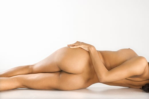 Back view of attractive nude woman lying on floor against white background. : Stock Photo