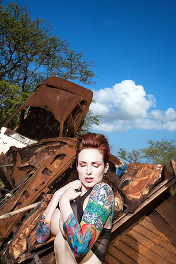 Partially nude attractive tattooed Caucasian woman standing in junkyard. : Stock Photo
