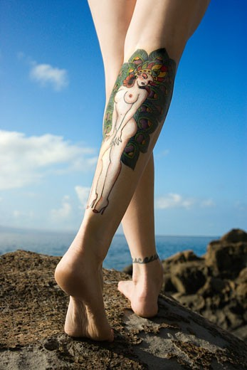 Stock Photo: 1525R-107711 Back view of Caucasian woman's legs covered with sexy tattoo.