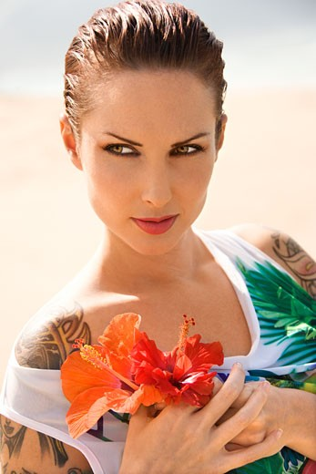 Attractive Caucasian tattooed woman holding Hibiscus flowers in Maui, Hawaii, USA. : Stock Photo