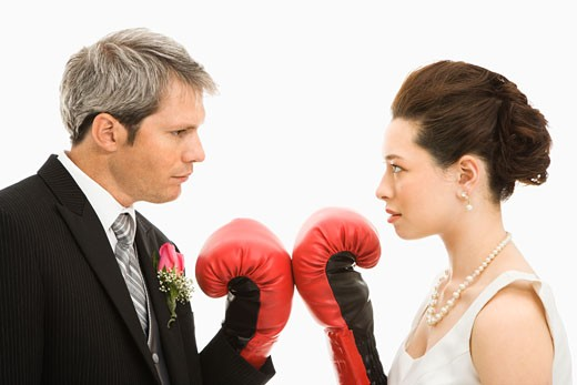 Caucasian groom and Asian bride wearing boxing gloves. : Stock Photo