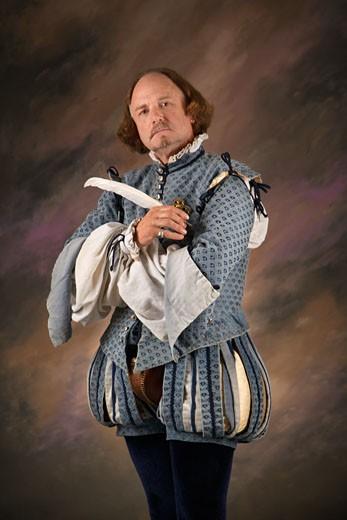 William Shakespeare in period clothing holding feather pen and looking at viewer. : Stock Photo