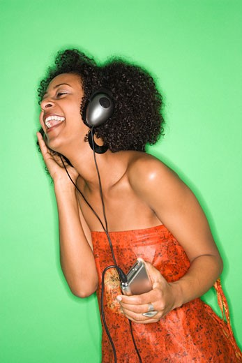 African-American woman listening to music through headphones. : Stock Photo