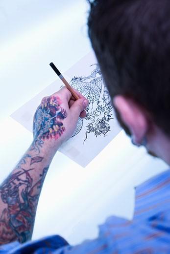 Caucasian male tattoo artist drawing tattoo on light table. : Stock Photo