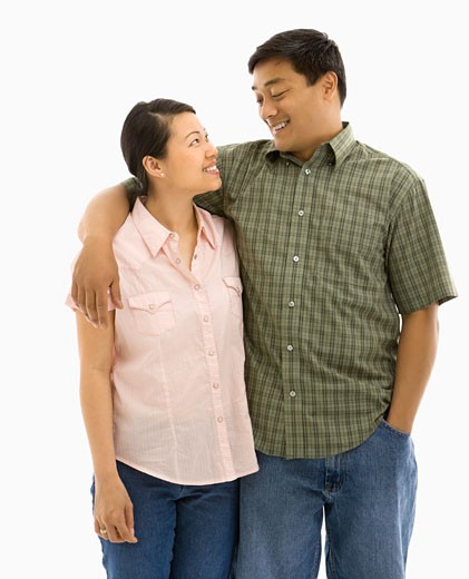 Mid adult Asian couple standing with arms around eachother and smiling at one another. : Stock Photo