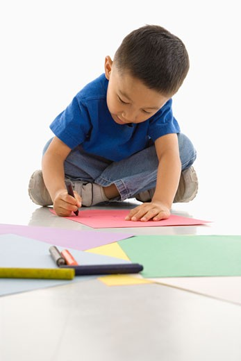 Stock Photo: 1525R-108445 Asian boy sitting on floor coloring on paper.