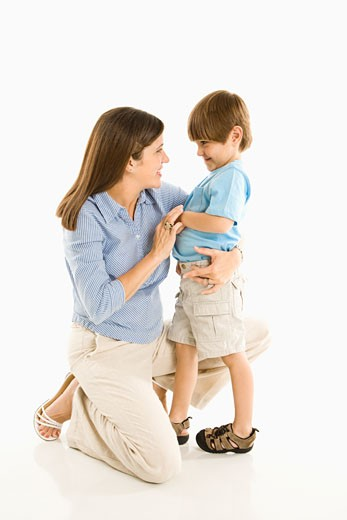 Stock Photo: 1525R-108565 Mother kneeling down with son against white background.