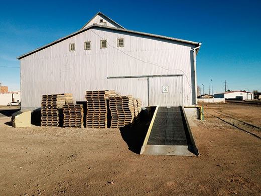 Storage warehouse with ramp and palettes in rural setting. : Stock Photo